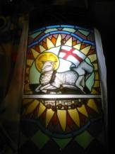 Baranek Boży z flagą białą z czerwonym krzyżem siedzący na księdze z 7-mioma pieczęciami