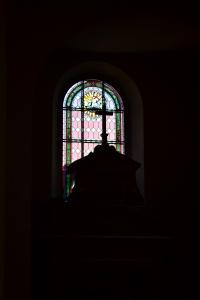 okno wypełnione motywem geometrycznym z medalionem z motywem Baranka Bożego