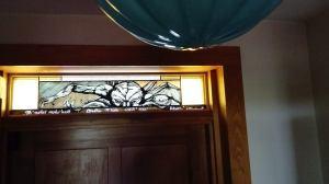 Straszliwy chtulhu wyłaniający się z dolnej krawędzi witraża. Ujęcie portretowe