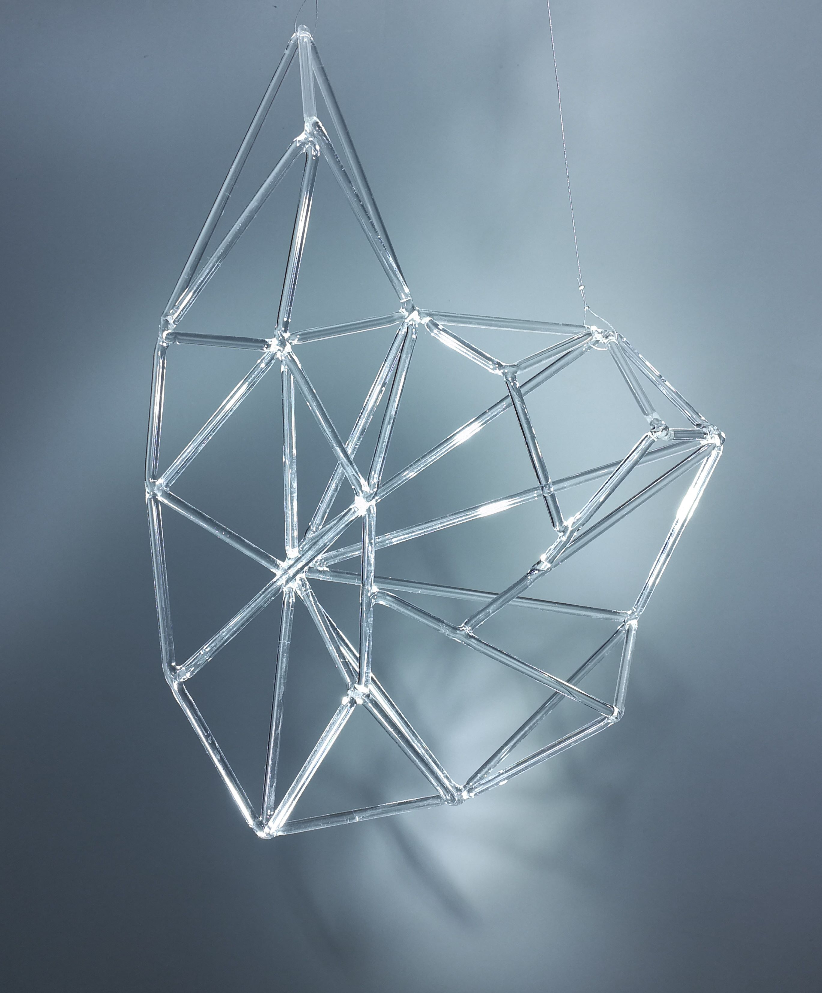 Rzeźba prętów szklanych na szaroniebieskim tle