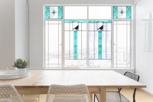 Prostota pomieszczenia podkreślona przez prostotę witraży w szkle białoprzeźroczystym i turkusowym z czarnymi sylwetkami ptaków.